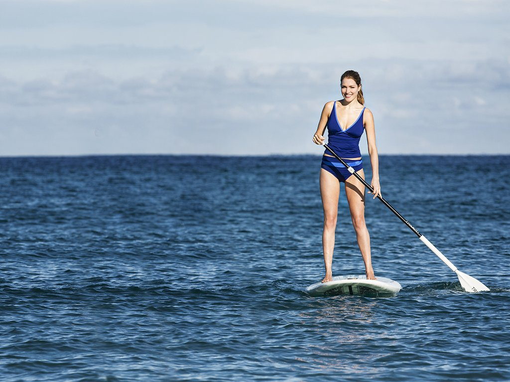 A guest enjoys paddle boarding at The Breakers