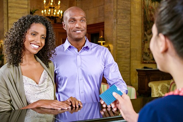 Smiling guests check-in at the Front Desk of The Breakers and receive their room key