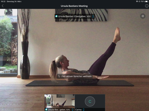 Connecting one Pilates enthusiast to another. Pilates instructor holding pose on a yoga mat on a wooden floor with legs at a 45 degree angle and hands lifted two feet off the ground wearing plum-colored yoga pant and multi-color athletic shirt and her blonde pony tail and ear buds exhibiting a slight sweat