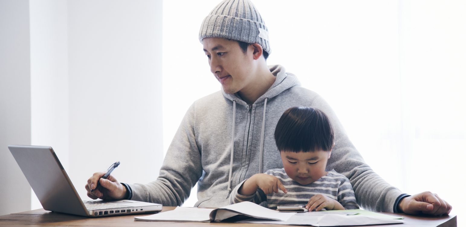 Embracing the rise of remote working. Japanese man in casual clothes using a laptop and his son using a smartphone on the desk. He's working and doing childcare at home.