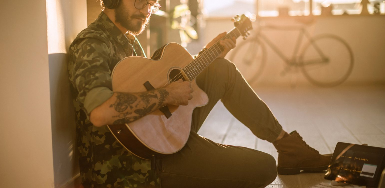 Young hipster man with tattoo sitting on floor and playing acoustic guitar