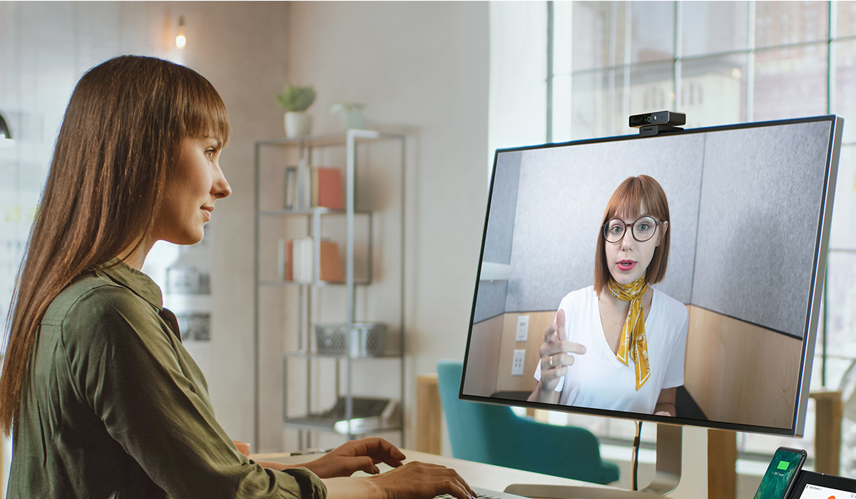 Woman sitting at her desk using video conferencing with a webex desk camera