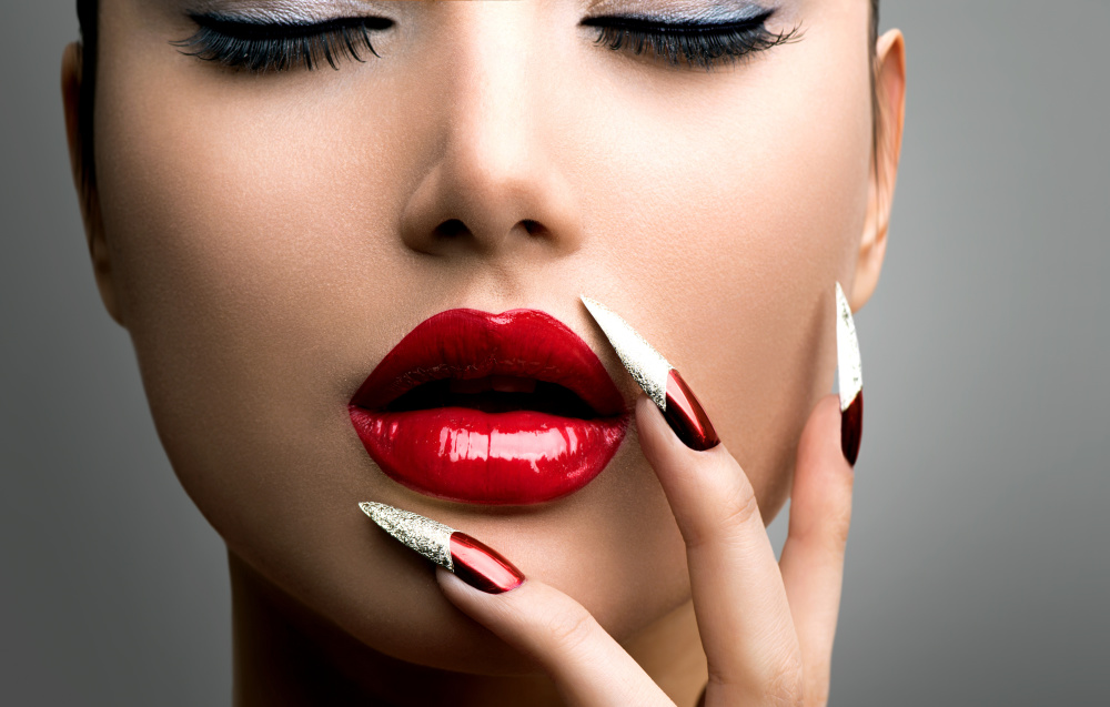 Model with red lips and long painted nails