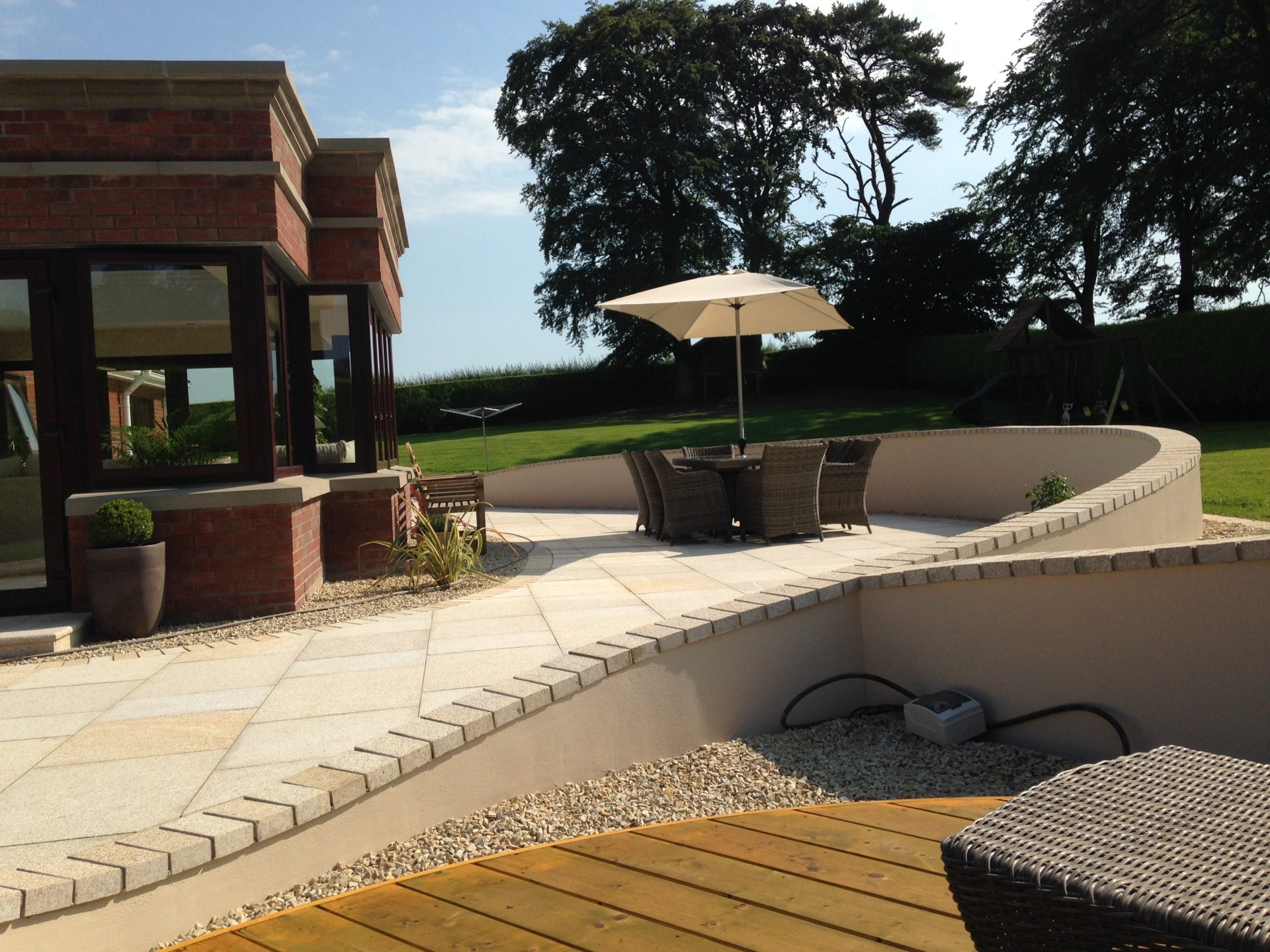 Yellow granite paving with curved wall surrounding the timber deck