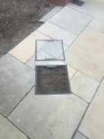 Yellow limestone paving, recessed manhole cover
