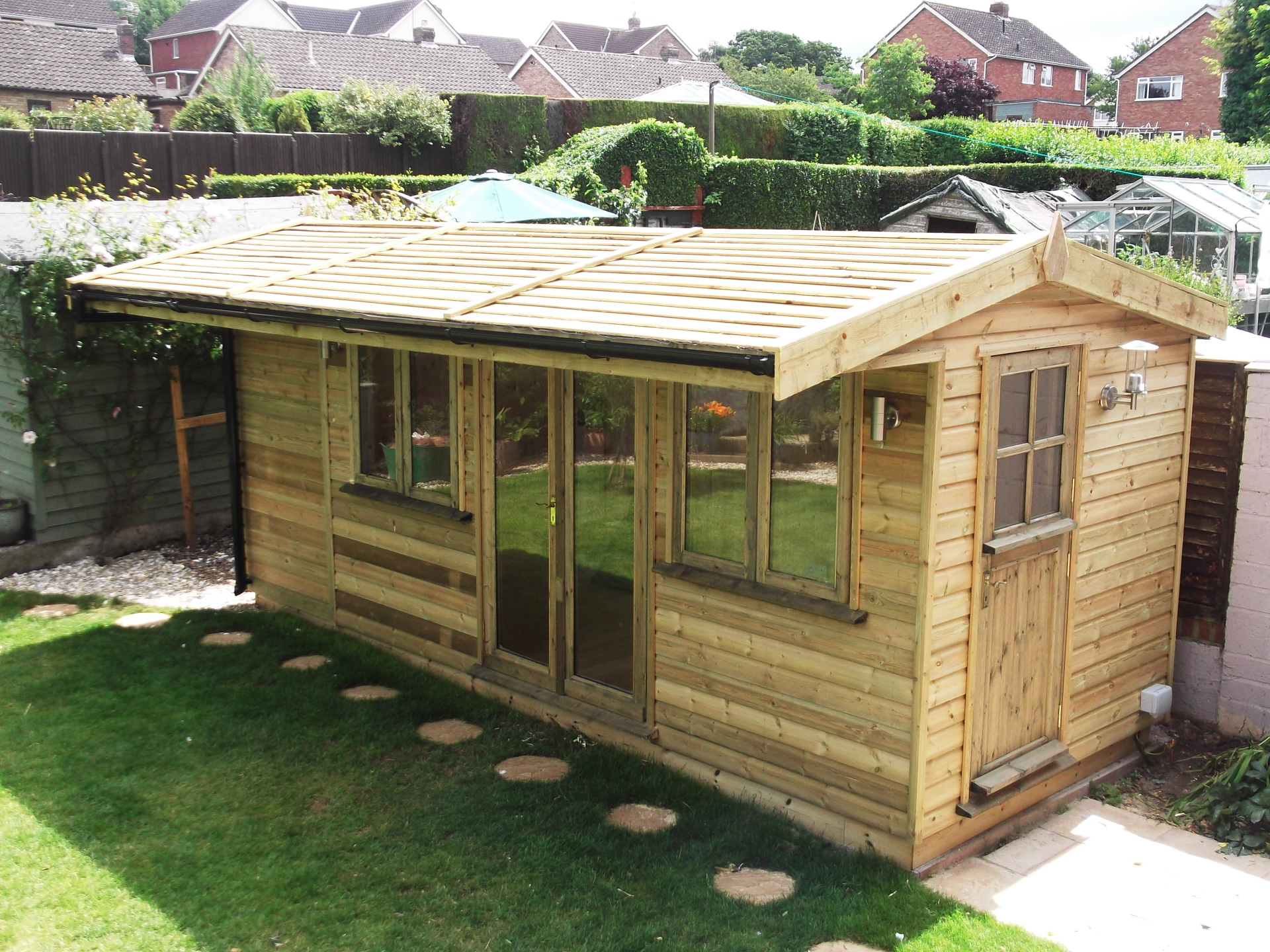 Garden building with log store.
