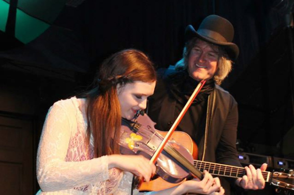 Chris Golden proudly watches daughter Elizabeth tearing up the fiddle.