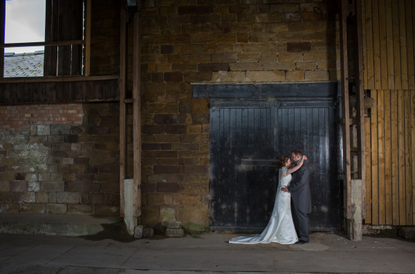 Married couple embracing in a warehouse