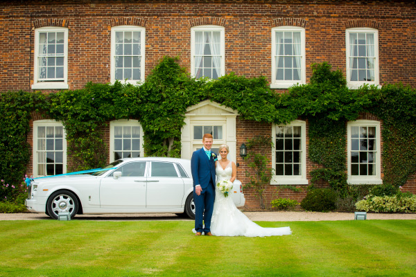 wedded couple posing with car and house