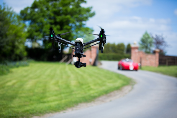 flying drone and blurred red car