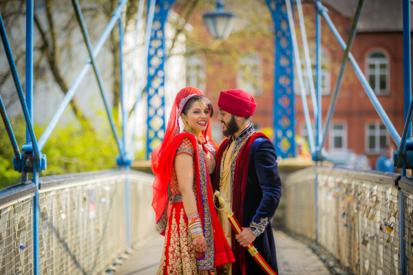 Asian couple smiling on a bridge