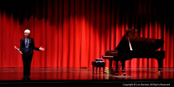 Photo of lady announcing a performer a a piano recital at suziki workshop in san marcos texas by luis ramirez
