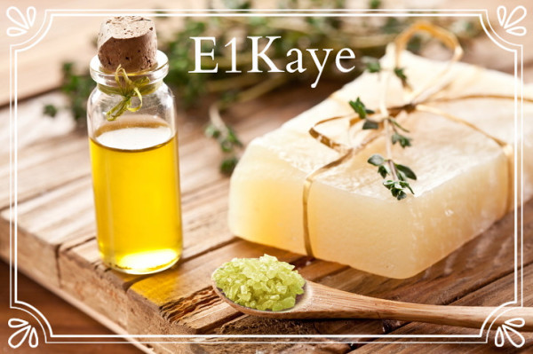 E1Kaye soap bar in a wooden table with a bottle of perfume oil on the left side