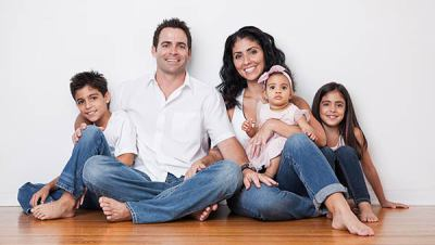 Kelly Jarrell Family Success, view of happy family sitting on the floor at home