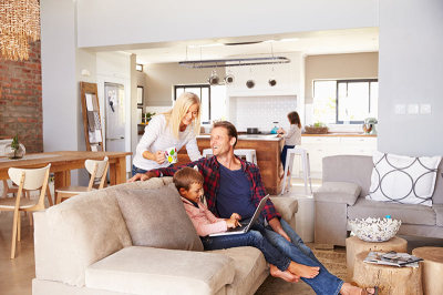 Kelly Jarrell Family Success, view of happy family sitting on sofa at home