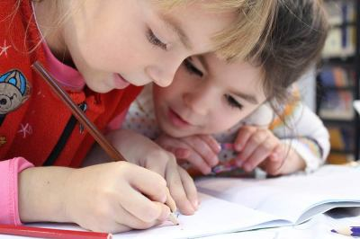 Kelly Jarrell Family Success, view of two happy children writing on notebook