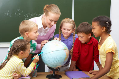 Kelly Jarrell Family Success, kids at school with techer looking at a globe