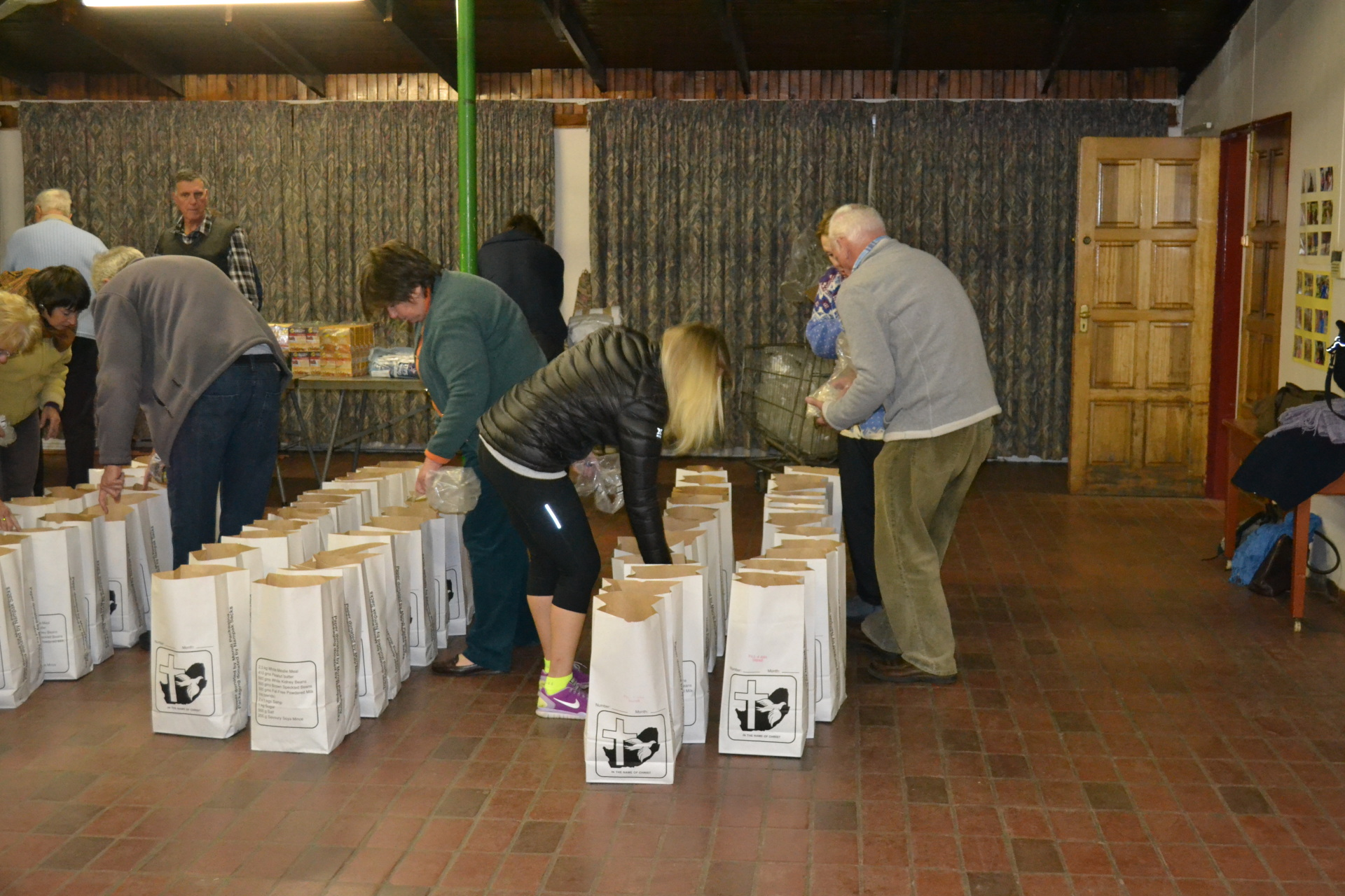 Volunteers packing bags at one of the monthly pack meets