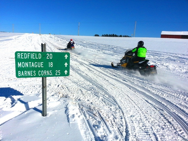 two snowmobile riders