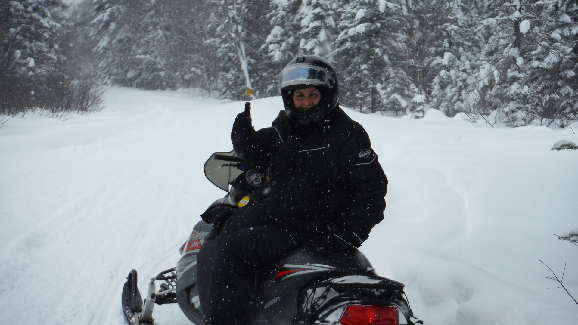 Debbie giving thumbs up on snowmobile