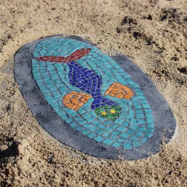 Tiled 'discovery' mosaic in a sand pit