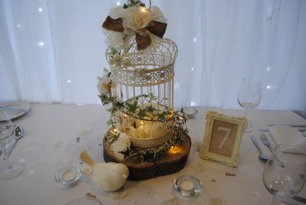 Vintage cream birdcage on log slice with burlap and lace ribbons