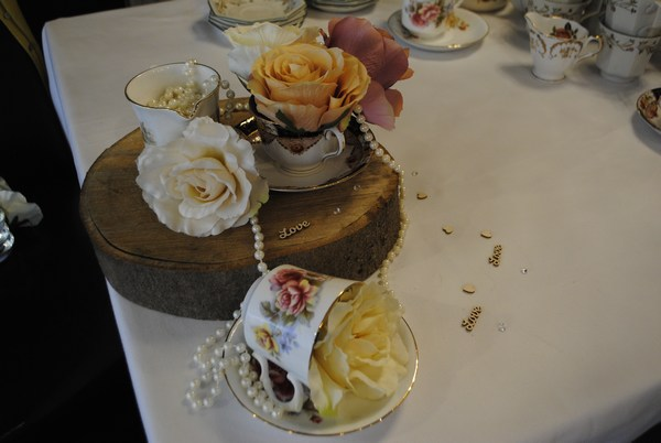 Teacups roses & draped pearls on log slice