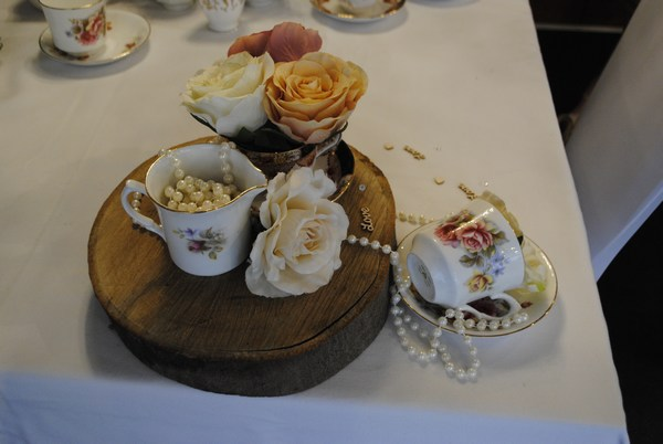 Teacups with roses & draped pearls on log slice