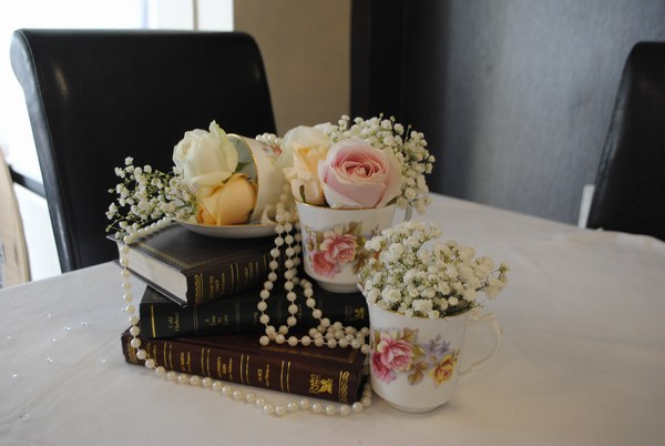 Teacups, fresh roses & draped pearls on trio of books