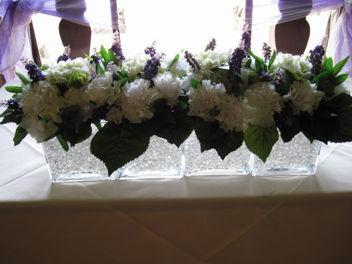 Top/civil table decoration in mixed artificial flowers on glass squares