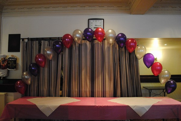 single pearl balloon arch in cadbury & hot pink behind buffet table