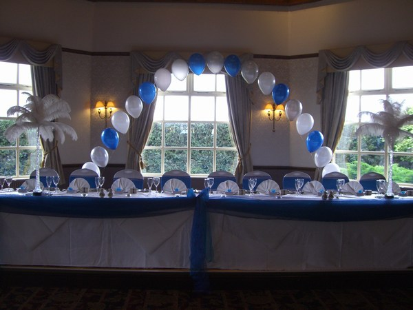 single pearl balloon arch in royal blue & white behind top table
