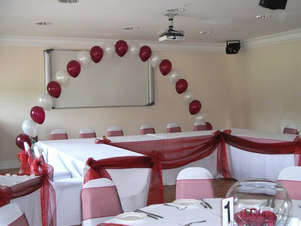 single pearl balloon arch in crimson & white behind top table