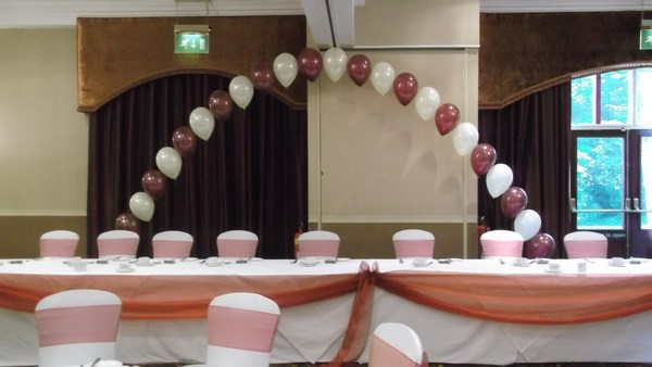 single pearl balloon arch in bronze & white behind top table