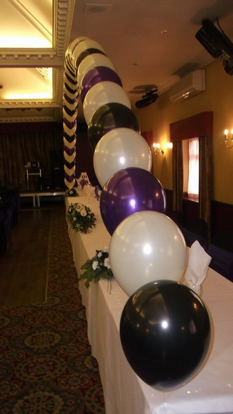 single pearl balloon arch in fornt of top table in cadbury white & black, close view