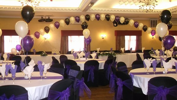 single pearl balloon arch in front of top table in cadbury white & black