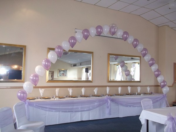 single pearl balloon arch in lilac & white behind top table