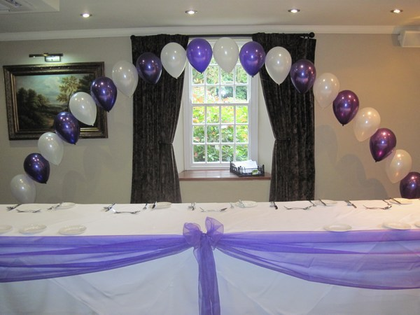 single pearl balloon arch in cadbury & white behind top table