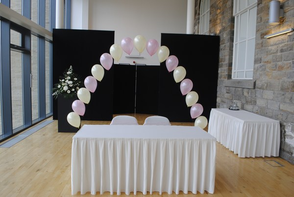 single pearl balloon arch in baby pink & white behind civil table