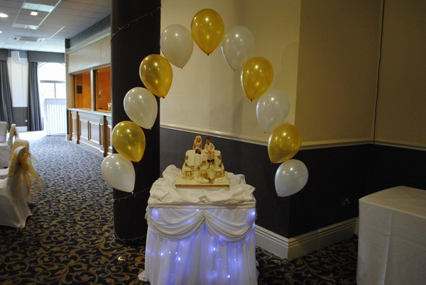 single pearl balloon arch in gold & white behind cake table