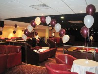 single pearl balloon arch in burgundy & white over stairs