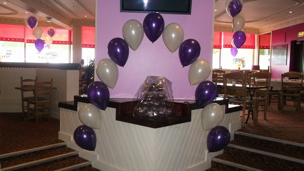 single pearl balloon arch in cadbury & white over the cake table