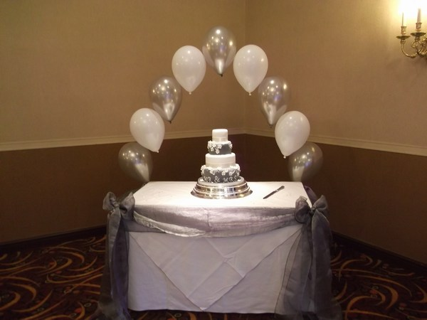 single pearl balloon arch in silver & white behing cake