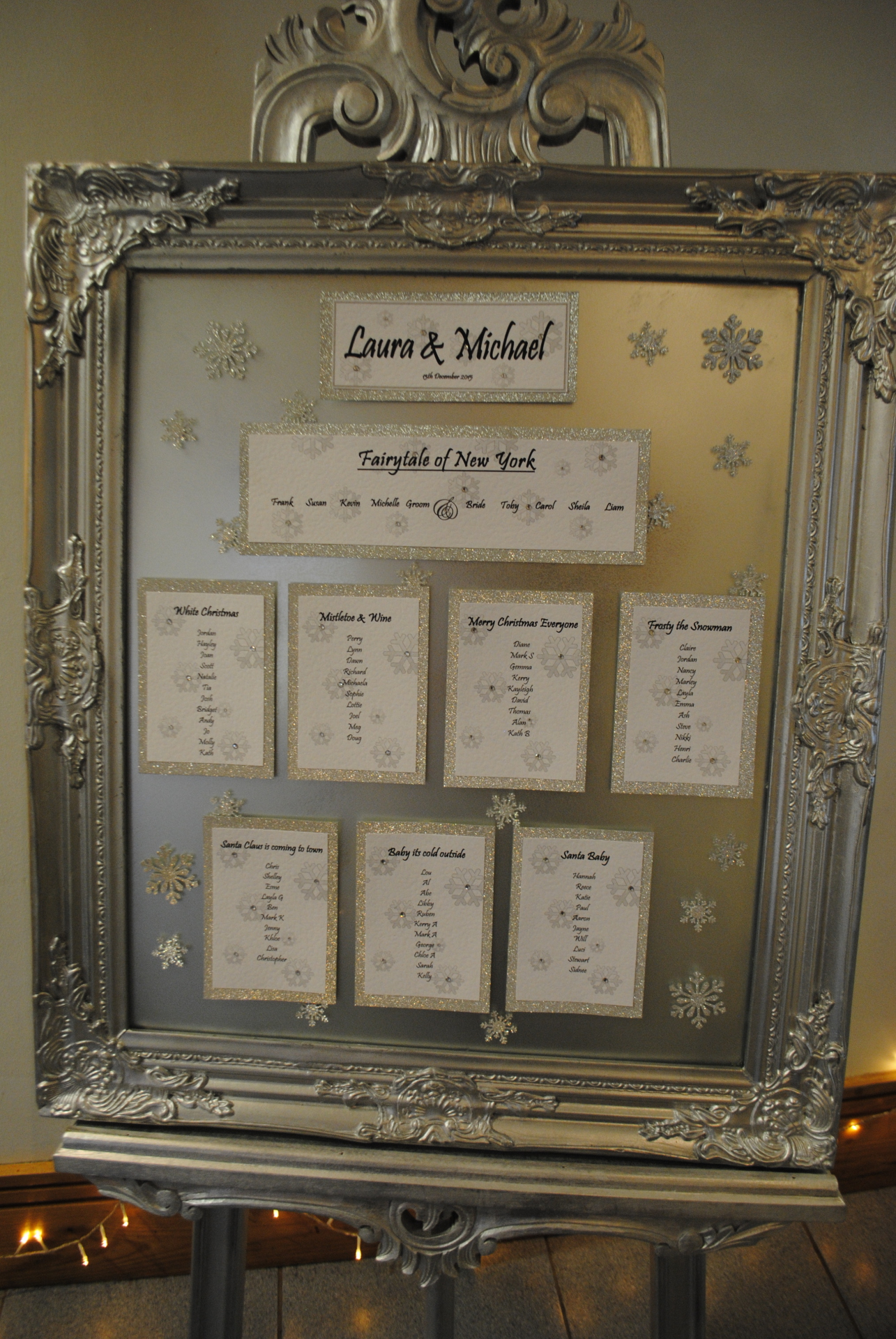 Snowflake table plan with silver glitter card on framed mirror