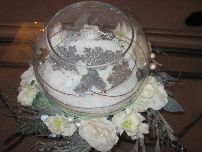 Large fishbowl with fake snow, silver snowflake and silver canes, with cream roses ring around base