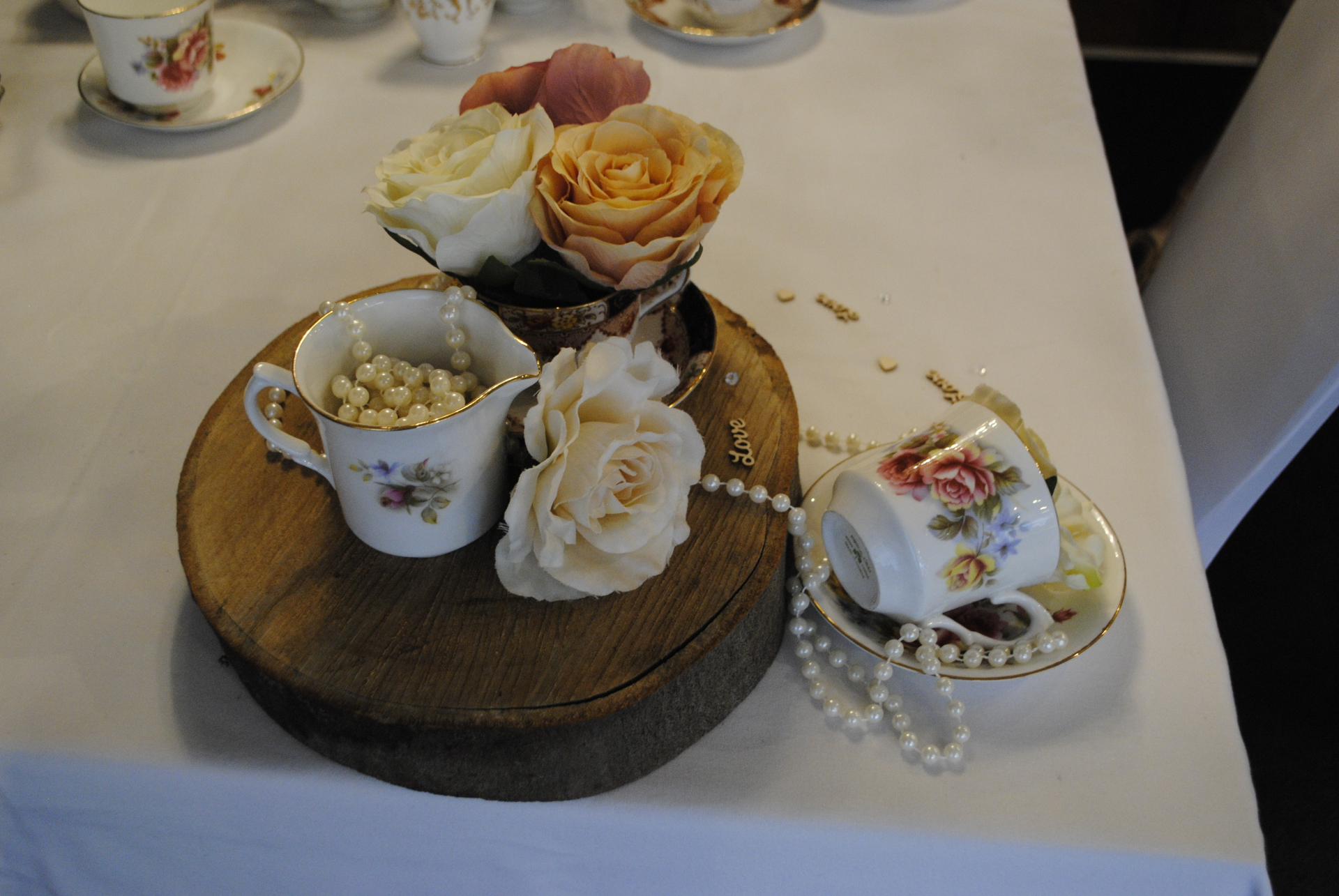 Vintage teacups with artificial roses draped pearls on a log slice