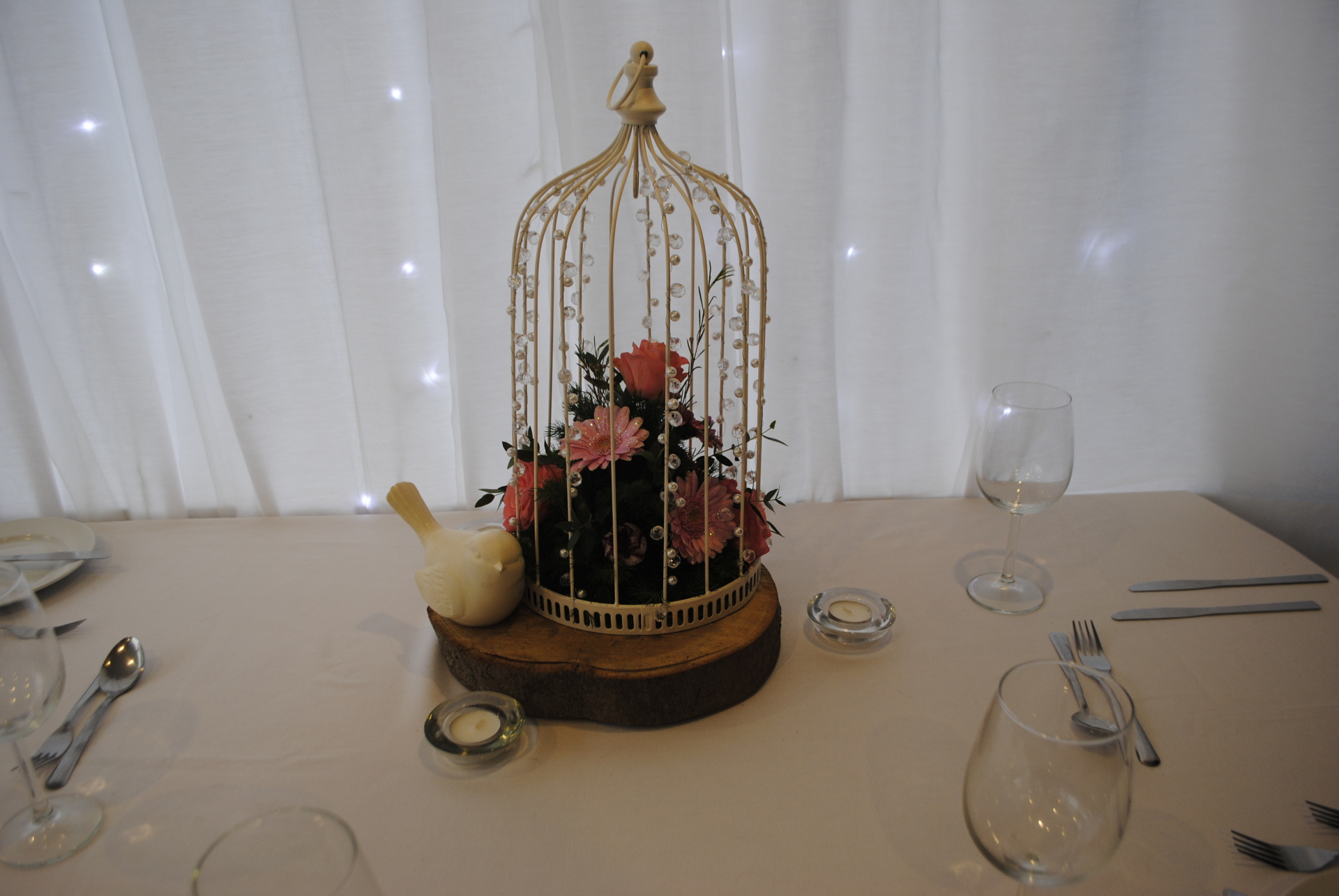 Beaded birdcage with fresh flowers and log slice