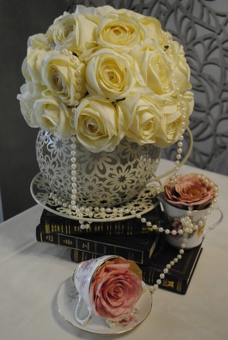 Giant teacups with cream rose dome and additional vintage teacups stacked on books