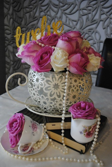 Giant teacups with fresh roses, stacked on books with additional teacups