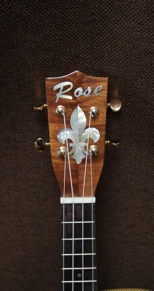 Koa concert-size ukulele, headstock flour-de-lis detail